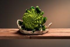 Green cauliflower in a wicker basket royalty free stock photos