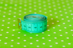 Green centimeter on a green background Stock Photo