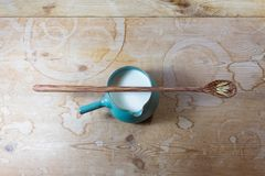 Green ceramic bowl pitcher of oat milk centered on rustic wood table, long wooden spoon with oat heads balanced on top. Horizontal aspect Royalty Free Stock Image