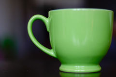Green ceramic coffee cup. Closeup of a green coffee cup, photographed on a brown table. Photo was taken indoors Stock Photo
