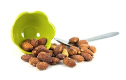 Green ceramic cup with almonds on white background. Royalty Free Stock Photo