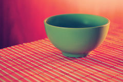 Green ceramic cup on a bamboo table cloth Royalty Free Stock Photo