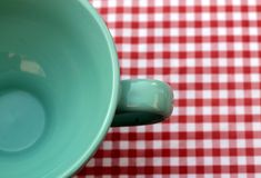 Green Ceramic Cup on Top of White and Red Checkered Print Textile Royalty Free Stock Photos