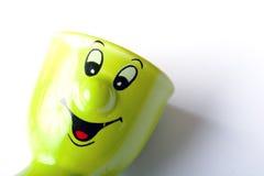 Green ceramic egg holder. Bright green ceramic happy face egg holder stock images