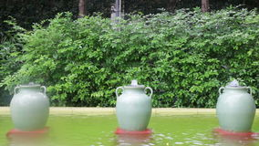 Green ceramic jar fountain decorated in garden stock video footage