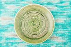 Green ceramic plate on the blue wooden background. Top view Stock Photos