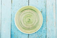 Green ceramic plate on the blue wooden background. Top view Royalty Free Stock Images