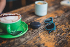 Green Ceramic Teacup With Coffee Beside Blue Framed Black Sunglasses on Top of Brown Wooden Table Royalty Free Stock Photos