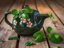Green ceramic teapot with fresh mint on a wooden table. Close up