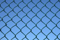 Green chain link fence. On a blue sky background royalty free stock photo