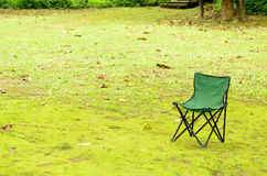 Green chair on green grass. Green camping chair on green grass Royalty Free Stock Photos