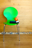 Green Chair, Red Apple and some Books. Against wooden wall / Modern interior Stock Images