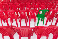 Green chair among red ones Royalty Free Stock Photos
