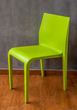 Green chair on the wooden floor. With the grey concrete wall Royalty Free Stock Photos