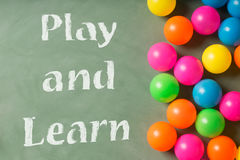 Green chalkboard and colorful balls. Play and learn Royalty Free Stock Photography
