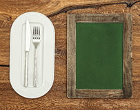 Green chalkboard with white plate, knife and fork. Vintage style Royalty Free Stock Images