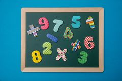 Green chalkboard with wooden frame, colorful math operation signs and numbers, blue background stock image
