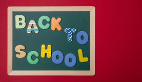 Green chalkboard with wooden frame, text back to school in colorful letters, red wall background stock photography