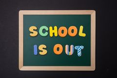 Green chalkboard with wooden frame, text school is out in colorful letters, black wall background. School is out concept. Green chalkboard with wooden frame royalty free stock images