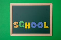 Green chalkboard with wooden frame, word school in colorful letters, green wall background stock photography