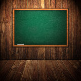 Green chalkboard in wooden interior Stock Photography