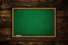 Green chalkboard in wooden interior Stock Images