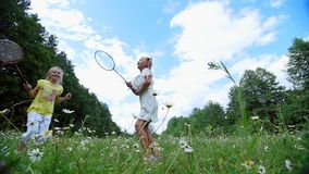On the green, chamomile lawn, Girls, children, playing badminton,. They run, jump, fool around. They have fun. Summer. Outdoors in the forest Vacation with stock footage