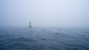 Green channel marker buoy in the fog royalty free stock photography