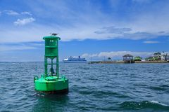 Green channel marker and cruise ship. Green channel marker near cruise ship docked in Newport Rhode Island Royalty Free Stock Photos