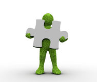 Green character holding a jigsaw piece Stock Image