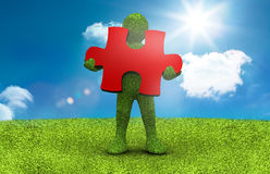 Green character holding a red jigsaw piece Stock Image