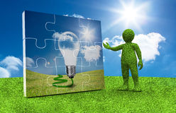 Green character presenting a jigsaw with light bulb inside Stock Photography