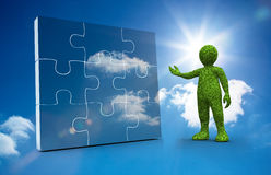 Green character presenting a jigsaw Stock Images