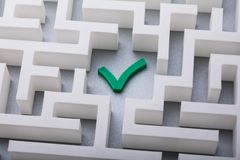 Green Check Mark Icon In The Centre Of Maze. High Angle View Of Green Check Mark Icon In The Centre Of White Maze stock images