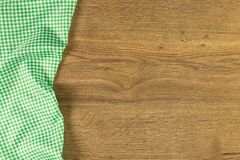 Green checkered cloth napkin on wooden background. Royalty Free Stock Photo