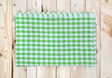 Green checkered tablecloth on wooden table, top view. Green checkered tablecloth on light wooden table, top view, copy space Royalty Free Stock Photo