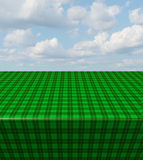 Green Checkered Tablecloth. Table with a blank empty picnic cloth in perspective with a plaid pattern on a blue sunny summer sky as a symbol of healthy food and Royalty Free Stock Photo