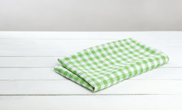 Green checkered tablecloth on white table background. White wooden table with tablecloth, background for the product montage Royalty Free Stock Photo