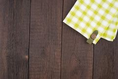 Green checkered tablecloth on wooden table. Top view Stock Photography