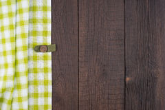 Green checkered tablecloth on wooden table. Stock Photos