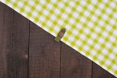 Green checkered tablecloth on wooden table. Royalty Free Stock Photos