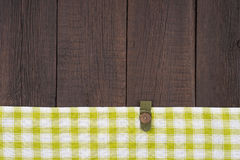 Green checkered tablecloth on wooden table. Royalty Free Stock Images
