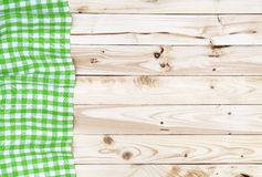 Green checkered tablecloth on wooden table, top view. Green checkered tablecloth on a light wooden table, top view Stock Photos