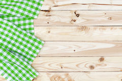 Green checkered tablecloth on wooden table, top view Royalty Free Stock Images