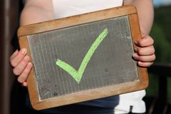 Green checkmark. Sketched with chalk on slate shown by young female Royalty Free Stock Photos