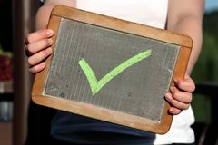 Green checkmark. Sketched with chalk on slate shown by young female Stock Photo