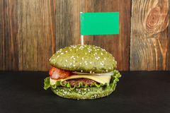 Green cheeseburger with flag close-up. Green cheeseburger with flag on wood background close-up Stock Images