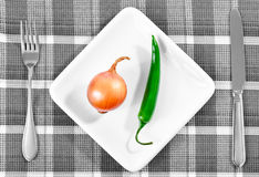 Green chili pepper and onion on a white plate Royalty Free Stock Photos