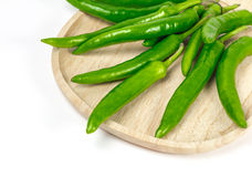 Green chili pepper on the wooden plate, isolated. On the white background Royalty Free Stock Photos