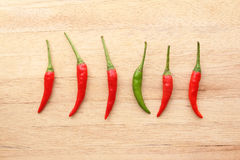 Green chilli amongst red chillies Stock Photo